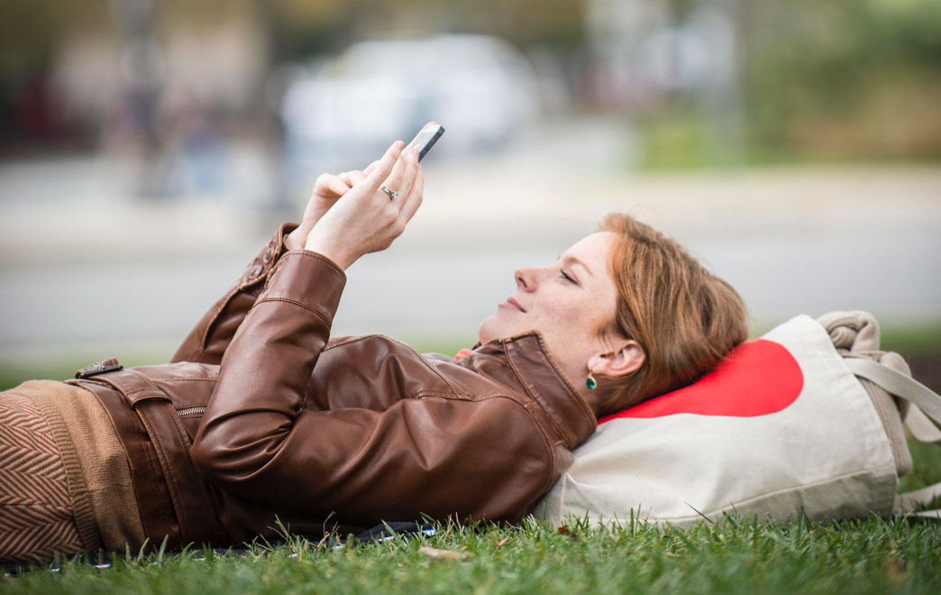 Woman laying on grass scrolling through her phone